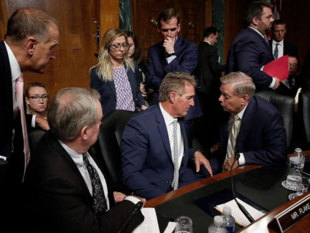 PHOTO: Republican members of the Senate Judiciary Committee and staff surround Sen. Jeff Flake, center, at the end of the Kavanaugh confirmation hearings, Sept. 28, 2019. From left to right are Sen. Thom Tillis,Sen. Mike Crapo, and Sen. Lindsey Graham.