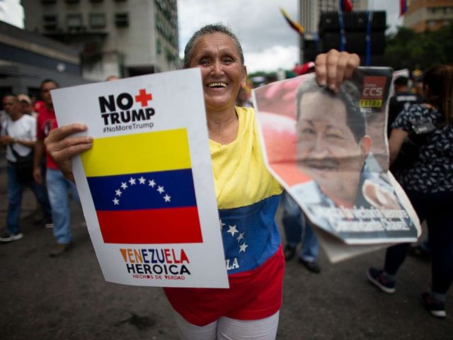 PHOTO: A supporter of President Nicolas Maduro holds a poster that in Spanish reads No more Trump and an image of Late President Hugo Chavez, during an anti-imperialist rally in Caracas, Venezuela, August 31, 2019.