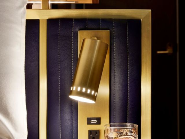 PHOTO: Lined in brass, a custom quilted leather-look headboard features a custom brass sconce and a crystallized glass ledge that easily holds overnight accessories.