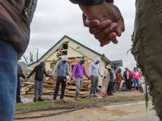 PHOTO: Residents of Talbotton, Ga., pray together outside a home destroyed by a tornado the day after storms battered Alabama and Georgia, March 4, 2019.