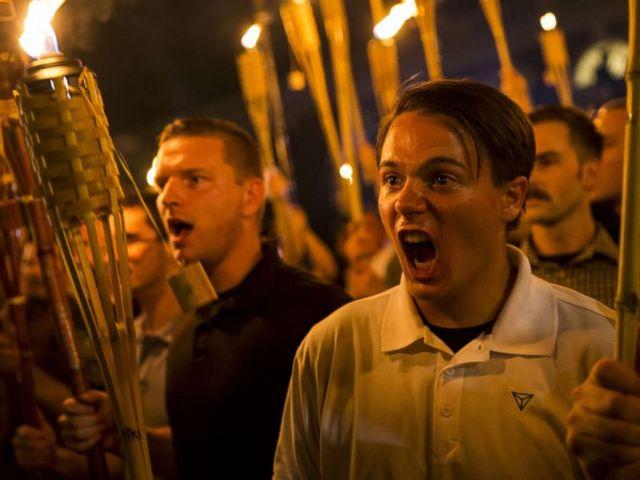 PHOTO: Peter Cvjetanovic marche avec des nationalistes blancs et des extrémistes d'extrême droite alors qu'ils encerclent la base d'une statue de Thomas Jefferson après avoir défilé sur le campus de l'Université de Virginie avec des torches à Charlottesville, en Virginie, le 11 août 2017.
