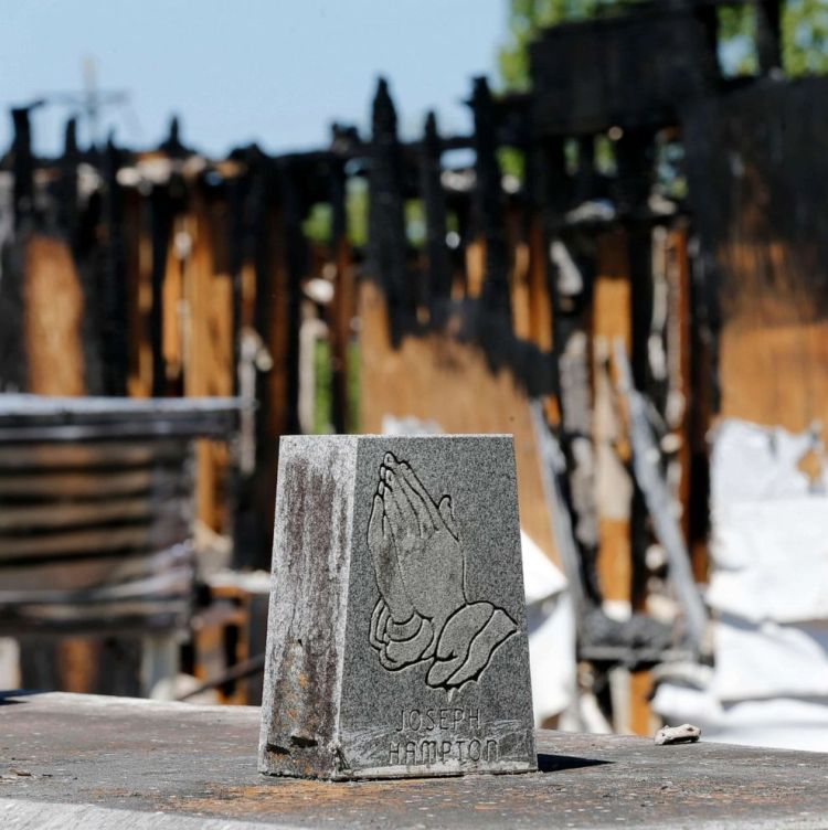 Graves from a cemetery are seen behind the burnt ruins of the Greater Union Baptist Church, one of three that recently burned down in St. Landry Parish, are seen in Opelousas, La., April 10, 2019.