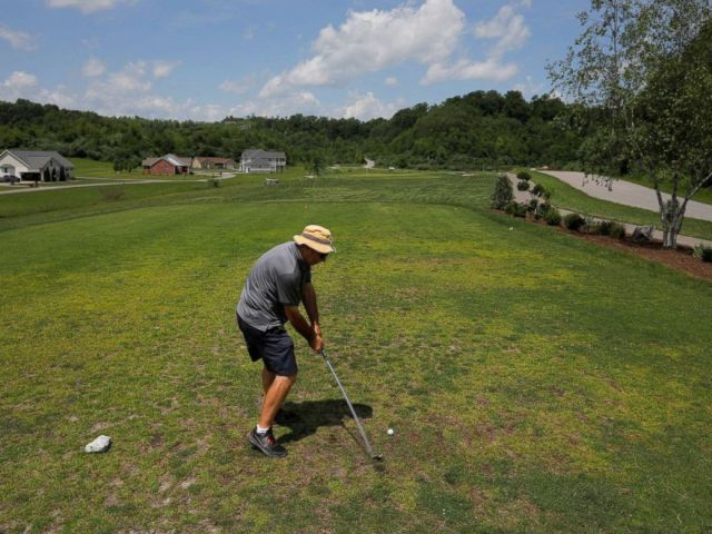 PHOTO: A man plays on a golf course built on the site of a former strip surface coal mine in Jenkins, Ky., May 20, 2018.