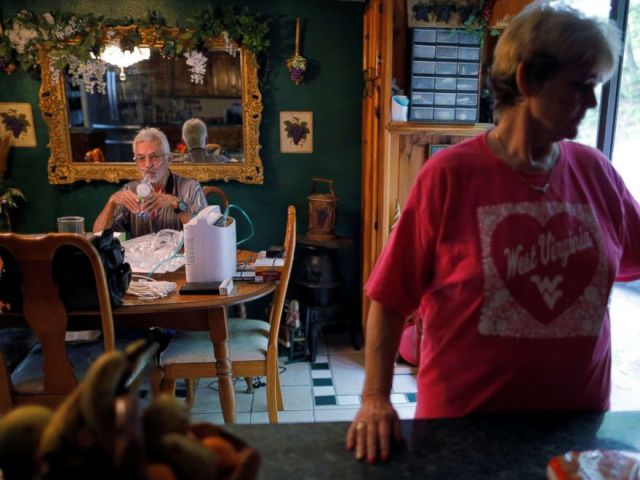 PHOTO: Retired coal miner Kennith Adams, who has complicated black lung disease and lives connected to an oxygen supply 24-hours a day, inhales medicine while his wife Tammie keeps him company, at their home in Princeton, W.Va., May 17, 2018.