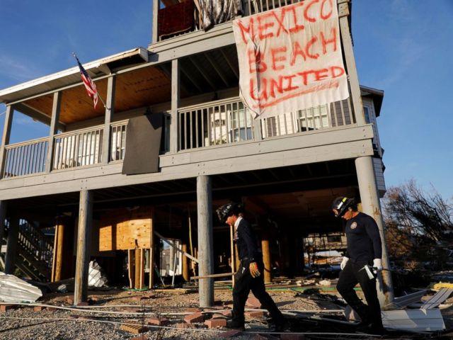 PHOTO: Une bannière est suspendue à une maison endommagée alors qu'une équipe de recherche et sauvetage en milieu urbain dans le sud de la Floride vérifie la présence des survivants de l'ouragan Michael à Mexico Beach, en Floride, le vendredi 12 octobre 2018.