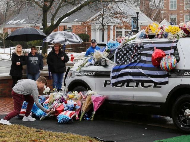 PHOTO: Mourners leave flowers on a police cruiser parked in front of City Hall in Westerville, Ohio, on Feb. 11, 2018. Westerville police officers Anthony Morelli and Eric Joering were killed in the line of duty on Feb. 10, 2018.