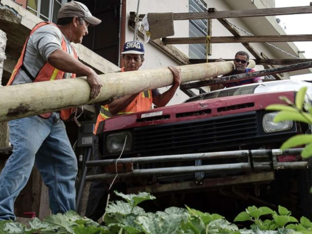 PHOTO: Retired carpenter Felipe Rodriguez, far right, uses his pickup truck to help municipal workers, who are also locals, move an electric post so they can install it near a home, in the El Ortiz sector of Coamo, Puerto Rico, Jan. 31, 2018.