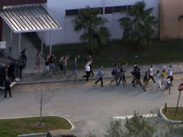 PHOTO: People emerge from a building with their hands raised after reports of a shooting at Stoneman Douglas High School in Parkland, Fla., Feb. 14, 2018.