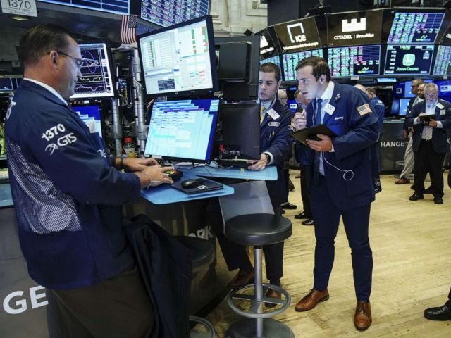 PHOTO: Traders and financial professionals work on the floor of the New York Stock Exchange at the opening bell on August 15, 2019, in New York.