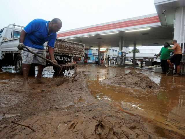 PHOTO: Residents remove mud from a gas station during a rain storm caused by Tropical Storm Karen in Barataria, Trinidad and Tobago, Sept. 22, 2019.