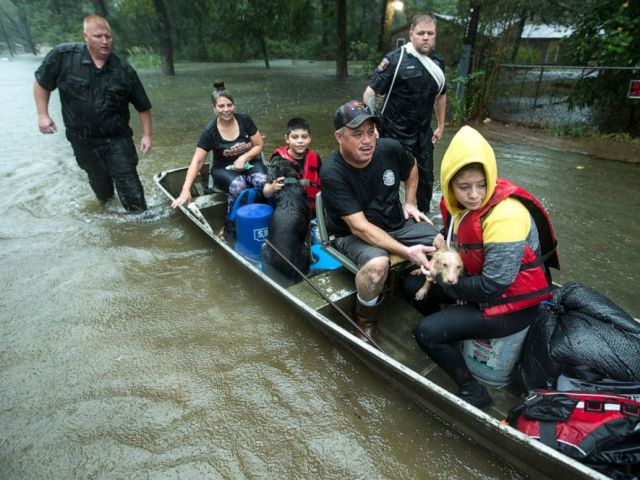 PHOTO: Police officers Lt. Troy Teller, left, and Cpl. Jacob Rutherford guide a boat carrying Maria, Ramiro, Jr., Ramiro and and Veronica Lopez from their flooded neighborhood, Sept. 19, 2019, in Spendora, Texas.