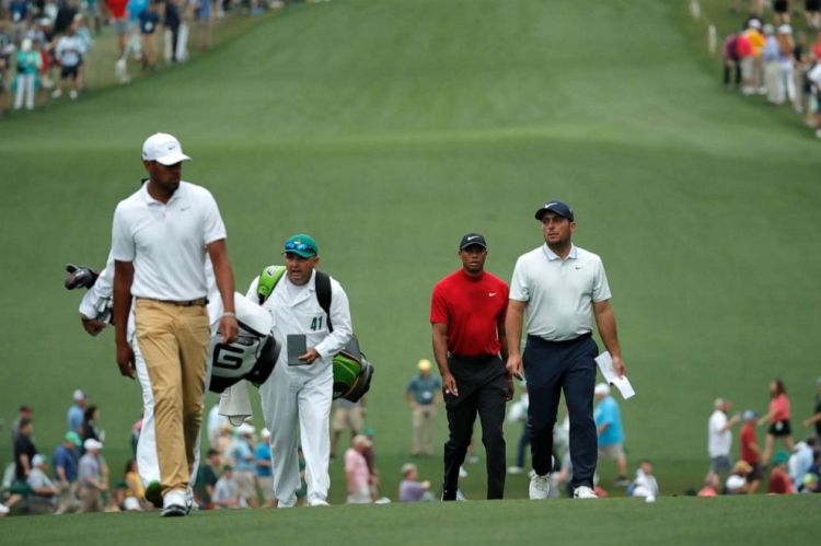 Francesco Molinari, Tiger Woods and Tony Finau walk up the first fairway during final round play at the Masters in Augusta, Ga., April 14, 2019.