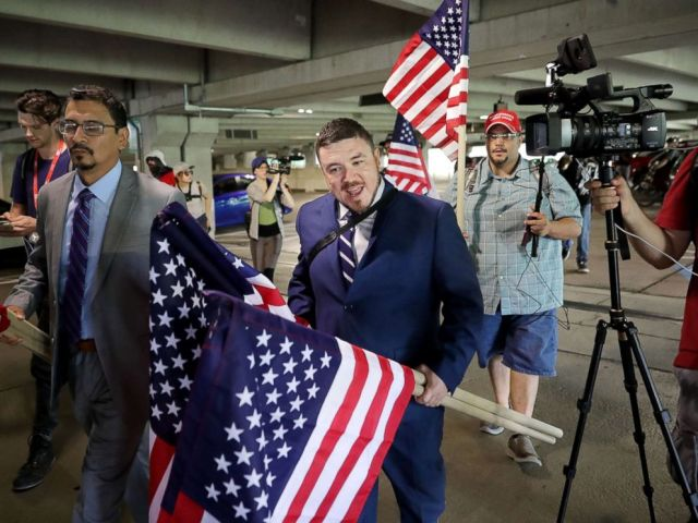 PHOTO: Surrounded by his supporters, reporters, and Fairfax County Police, Jason Kessler walks toward the Vienna/Fairfax GMU Metro Station to travel to the White House for his white supremacist Unite the Right rally, Aug. 12, 2018, in Vienna, Virginia.