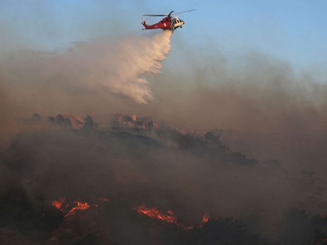 PHOTO: A firefighting helicopter works the Saddleridge Fire on Oct. 11, 2019, near Porter Ranch, Calif.