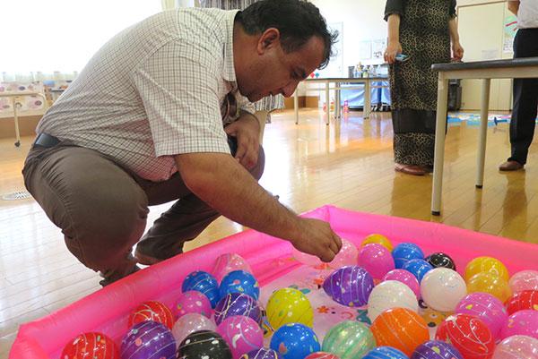 品川区台場小学校で行われた夏祭りの催し物、ヨーヨー釣りにチャレンジするアヒリディン氏