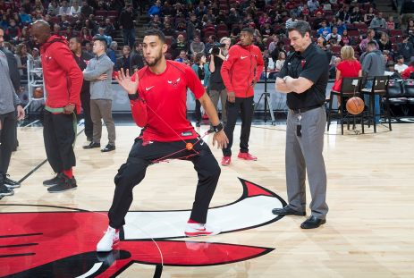 Chip Schaefer of the Chicago Bulls watches on as Denzel Valentine warms up pregame