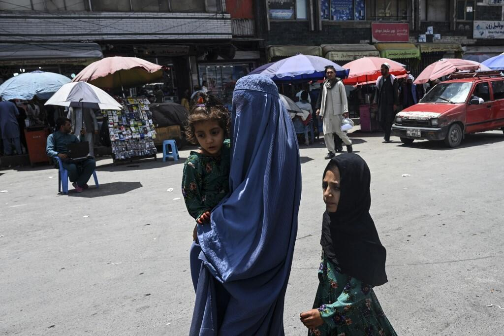 A woman in a burqa walks with her children in a market in Kabul on July 21, 2021.