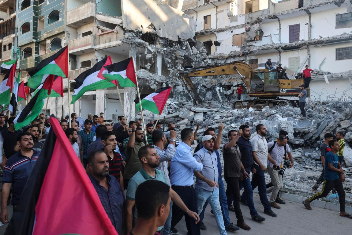 Palestinian protesters wave national flags in front of a building destroyed by Israeli airstrikes in Gaza City on June 15, 2021, during a protest by the ultra-nationalist Israeli Flag March in the Old City of Jerusalem, which celebrates the anniversary of the Israeli occupation of the eastern sector of Jerusalem in 1967.