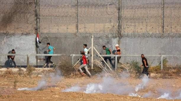 Manifestantes palestinos corren mientras caen botes de gases lacrimógenos disparados por las fuerzas de seguridad israelíes desde el otro lado de la frontera de Gaza, durante una manifestación junto a la valla fronteriza con Israel, al este de la ciudad de Gaza, el 21 de agosto de 2021.