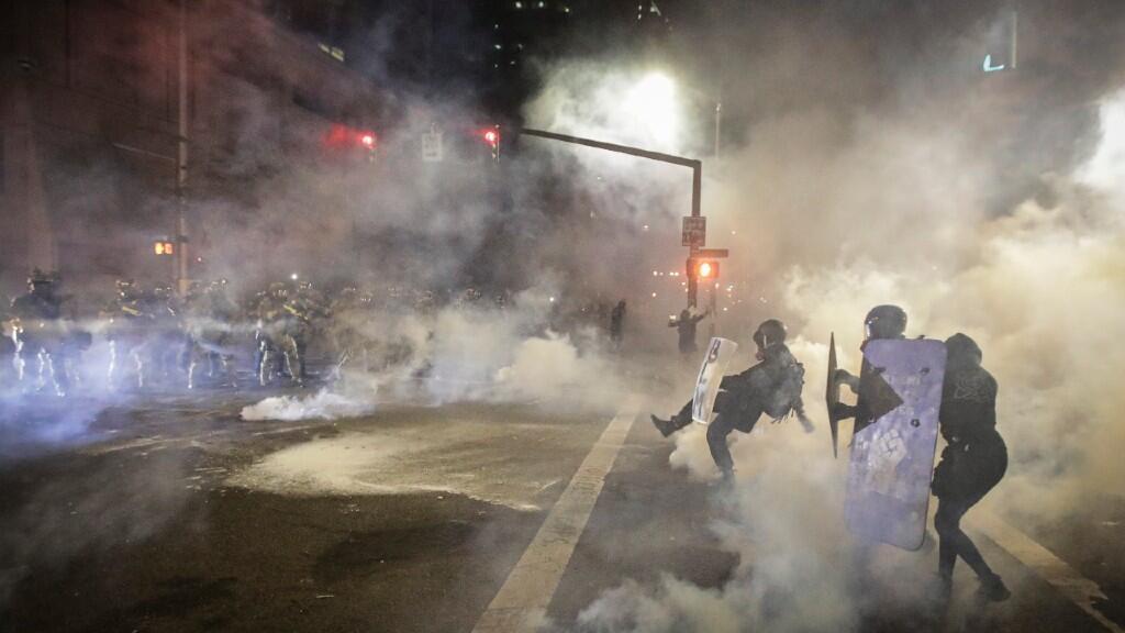 Un policía federal rechaza de una patada un bote de gas lacrimógeno lanzado por los manifestantes durante los disturbios en Portland. El 24 de julio de 2020.
