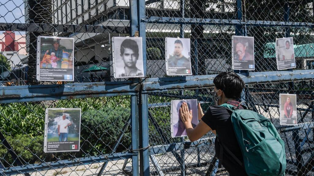 """Un activista cuelga una foto de un hombre desaparecido luego de levantar un """"anti-monumento"""" con motivo del décimo aniversario del San Fernando, en la Ciudad de México, el 22 de agosto de 2020."""