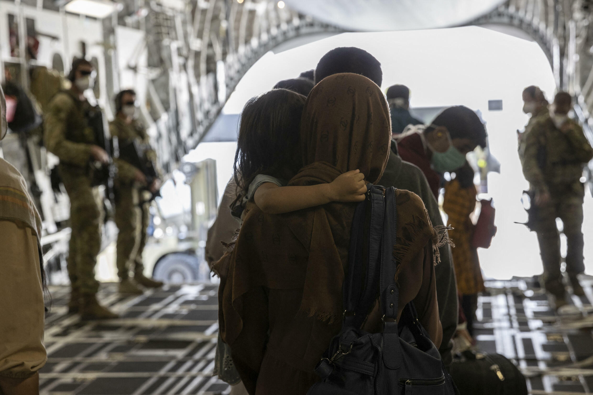 This photo taken on August 21 and received on August 22, 2021 from the Australian Defense Force shows people disembarking from a Royal Australian Air Force C-17A.  At least 7 people died on Saturday August 21 while trying to reach the Hamid Karzai airport in Kabul.