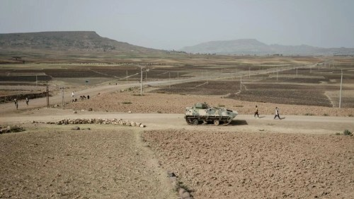 People walk near a tank of alleged Ethiopian army that is abandoned on the road near Dengolat, southwest of Mekele in Tigray region, Ethiopia, on June 20, 2021.