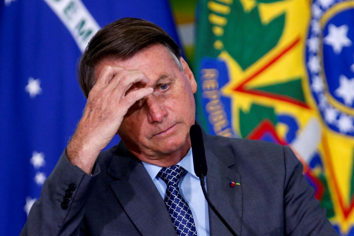 """File-Brazilian President Jair Bolsonaro reacts during the launch ceremony of the program """"Gigantes do Asfalto"""" to promote actions in the road freight transport sector, at the Planalto Palace, in Brasilia, Brazil, on May 18, 2021."""