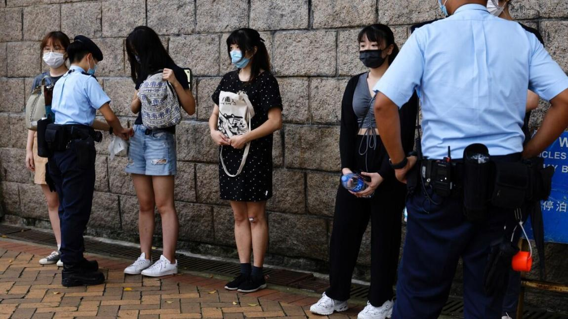 Supporters of Tong Ying-kit, the first person charged under a new national security law, are detained and searched by police during a High Court hearing in Hong Kong, China.  July 30, 2021.