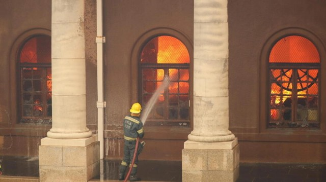 Firefighters battle flames as the library at the University of Cape Town burns after a bushfire broke out on the slopes of Table Mountain in Cape Town, South Africa, April 18, 2021.