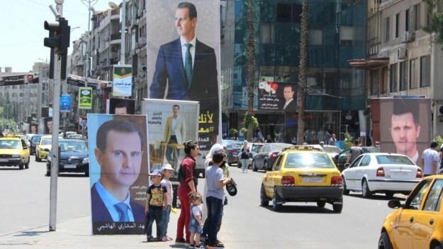 En esta imágen, un grupo de personas se encuentra cerca de carteles con la imagen del presidente sirio Bashar al-Assad, antes de las elecciones presidenciales del 26 de mayo, en Damasco, Siria, el 18 de mayo de 2021. Fotografía tomada el 18 de mayo de 2021.