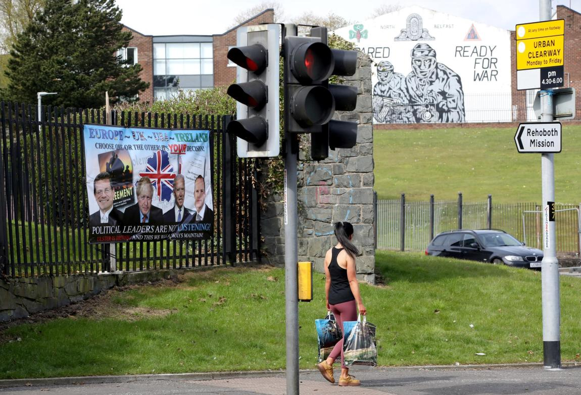A woman walks past a loyalist poster denouncing the Northern Ireland Protocol to the Brexit withdrawal agreement in Belfast on April 19, 2021.