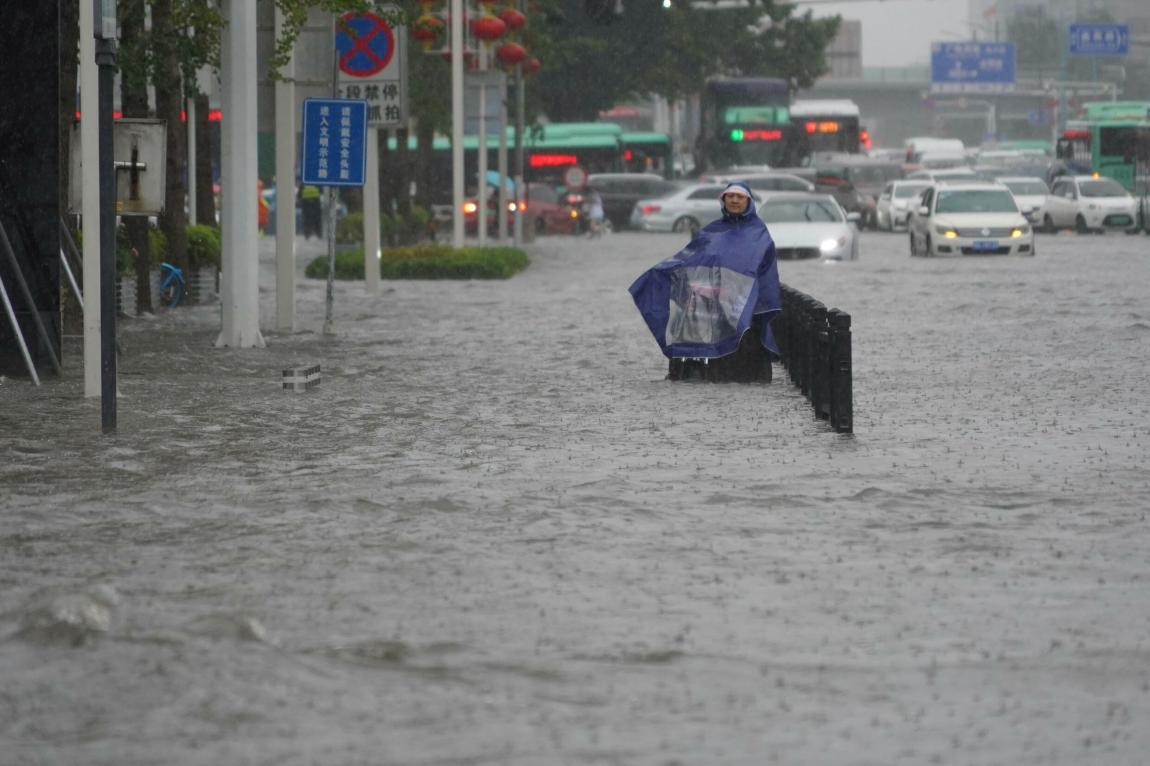 A resident in a rain cover stands on a flooded road in Zhengzhou, Henan province, China, on July 20, 2021.