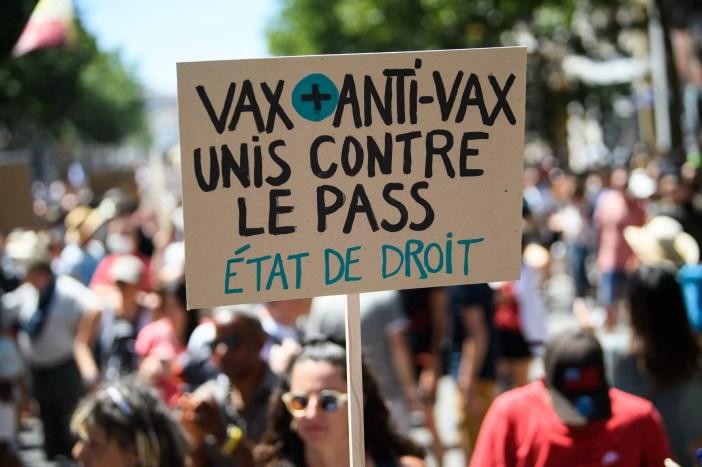 """Un manifestante sostiene una pancarta """"Vax y anti-vax unidos contra el pase. Estado de derecho"""" durante una manifestación en Marsella, el 17 de julio de 2021, contra las nuevas restricciones sanitarias en Francia."""