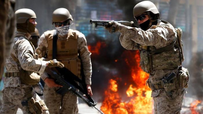 Un soldado apunta con su arma de fuego a los manifestantes que protestan contra el sistema económico chileno en Valparaíso. 21 de octubre de 2019.