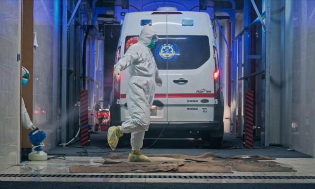 """Medical teams in Wuhan, China, get disinfected in a still from Ai Weiwei's """"Coronation""""."""