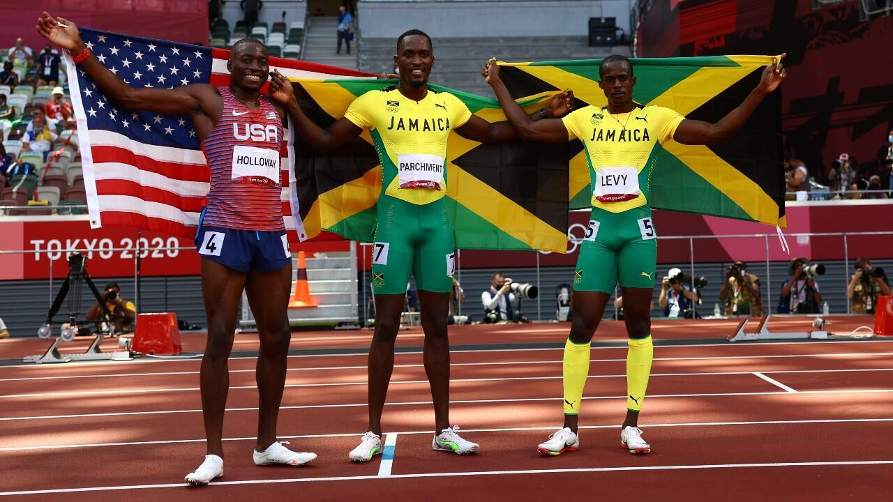 Jamaica's Hansle Parchment (center) poses with his country's flag after winning gold in the 110-meter hurdles event.  Next to him are silver medalist Grant Holloway of the United States and bronze medalist Ronald Levy.