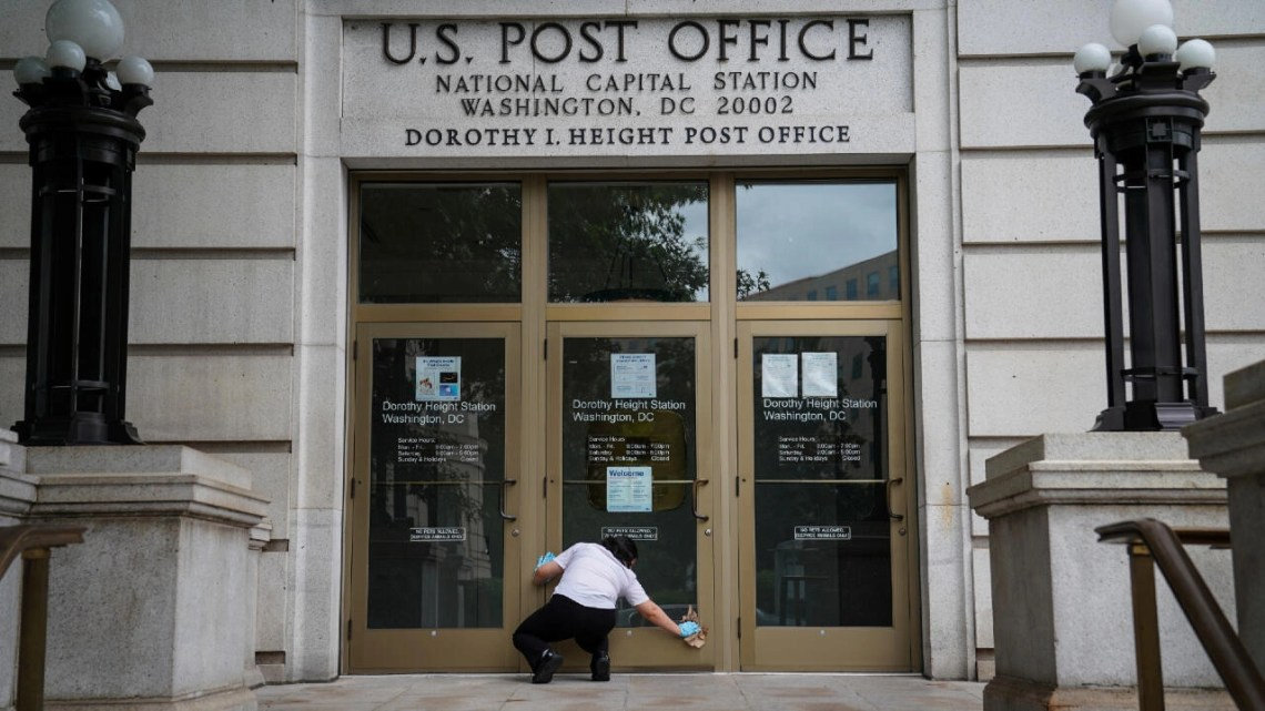 A woman cleans the doors of the National Capital Station US Post Office near Capitol Hill in Washington, DC, August 13, 2020.