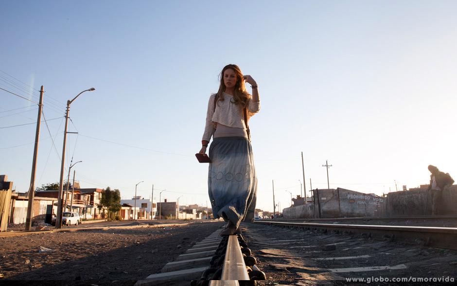 A atriz se equilibra nos trilhos da Peru Rail.
