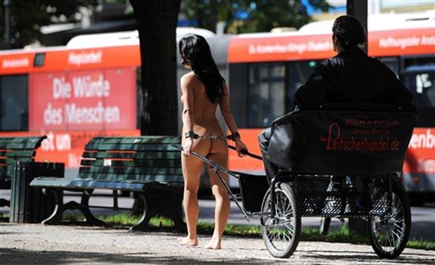 Mulher nua puxa carroça durante a gravação.