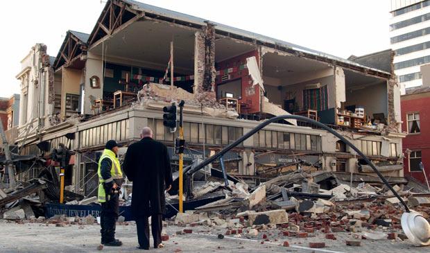 Homens observam prédio parcialmente destruído em Christchurch, na Nova Zelândia, após terremoto nesta sexta-feira (3)