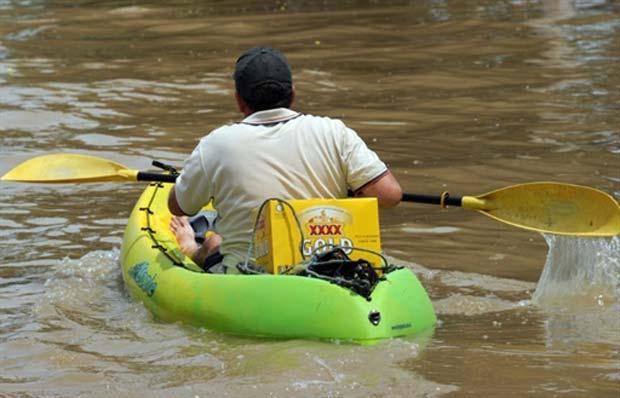 Um morador de Rockhampton, uma das cidades mais afetadas pelas inundações na Austrália, foi flagrado nesta quarta-feira (5) usando um caiaque para ir buscar cerveja. (Foto: Torsten Blackwood/AFP)