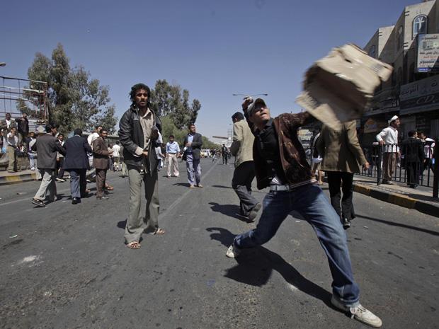 Um manifestante anti-governo atira uma pedra na direção de defensores do governo do Iêmen durante conflito em Sanaa, neste sábado (19). A repressão a protestos antigoverno no Iêmen provocaram mais mortes no Iêmen, onde manifestantes protagonizam protestos (Foto: AP)