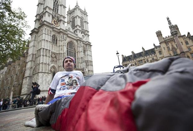 John Loughrey, fã da família real britânica, acampa com seu saco de dormir nesta terça-feira (26) em frente à Abadia de Westminster, ao fundo. Ele promete ficar no local até o casamento entre o Príncipe William e Kate Middleton, nesta sexta. (Foto: AFP)