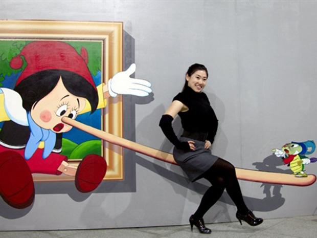 Mulher chinesa posa com uma pintura quadridimensional (4D) em uma exposição de arte contemporânea na província chinesa de Jilin, no sábado (14). A China ultrapassou a Grã-Bretanha como segundo maior mercado mundial de arte e antiguidades, em 2010, segundo relatório da Fine Art Fair Europeia (Tefaf). (Foto: AFP)