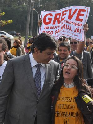 O ministro da Educação, Fernando Haddad, é abordado por professores da rede estadual em greve em Criciúma (SC) (Foto: Ulisses Job/Futura Press)