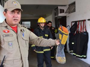 Bombeiro exibe bota que já está sem condições de uso, mas ainda é utilizada durante as ocorrências (Foto: Renato Bezerra/G1)