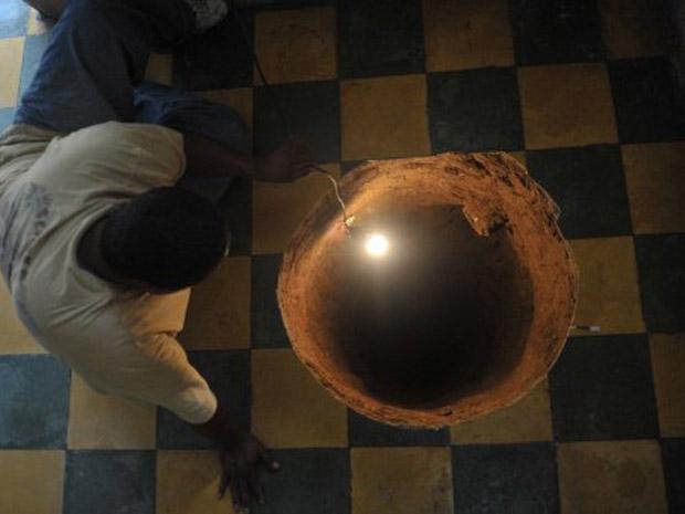 Homem observa buraco que apareceu dentro de casa nesta terça-feira (19) na Cidade da Guatemala. Os vizinhos ouviram uma explosão durante a madrugada e pensaram que se tratava de um botijão de gás. Em vez disso, apareceu um buraco de 12,2 metros de profundidade e 80 centímetros de diâmetro (Foto: AFP)