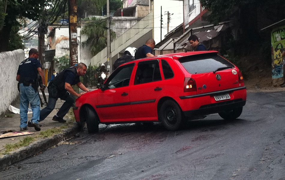 Por causa do óleo na pista, um carro não consegue fazer a curva na subida da comunidade. Policiais ajudaram a tirar o carro do local