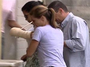 Jovem baleada no carro de Adriano chega à delegacia da Barra da Tijuca (Foto: Reprodução TV Globo)